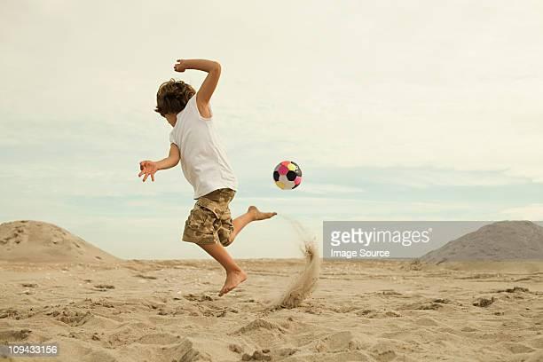 Garçons coup de pied de football sur la plage