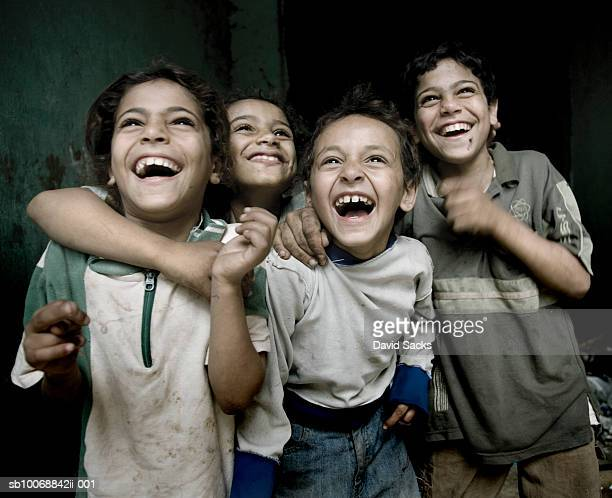 Boys (5-10) laughing with arms around each other