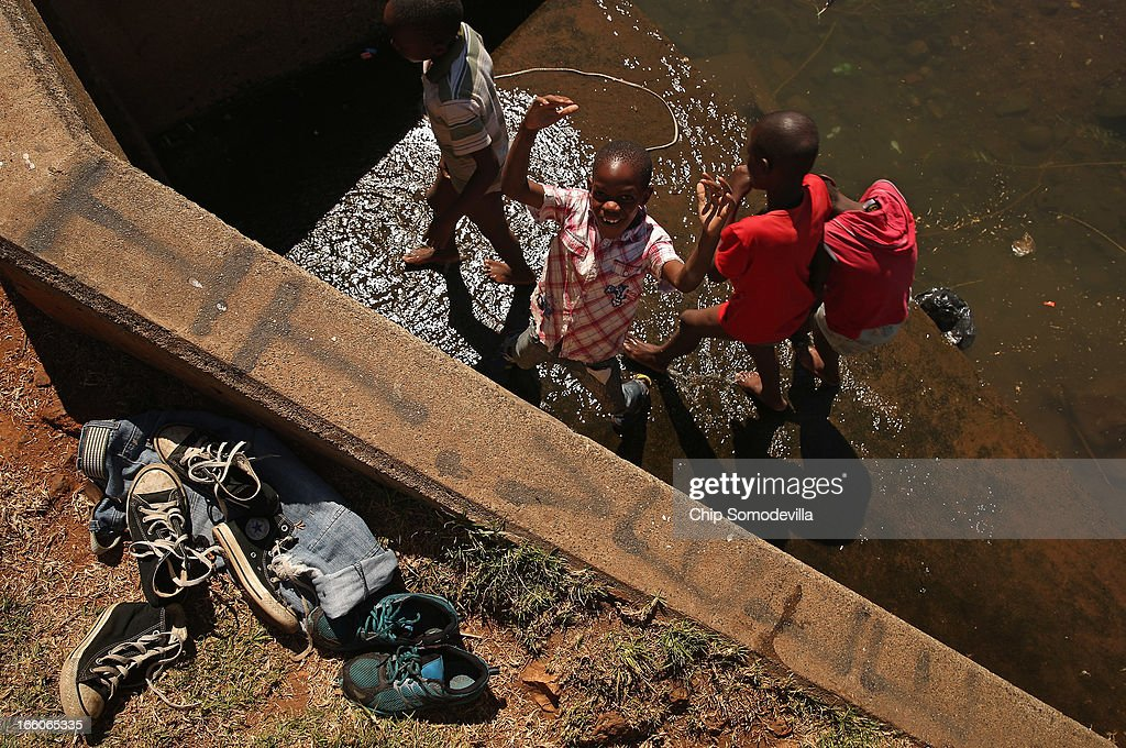 Boys leave their clothes aside while playing in a large culvert in Thokoza Park April 8, 2013 in Johannesburg, South Africa. Thokoza Park is situated right next to Regina Mundi Catholic Church, a site of resistance during apartheid and place of shelter during the 1976 Soweto Uprising. Former South African President Nelson Mandela returned to his Johannesburg home Saturday after spending nine days in the hospital with pneumonia.