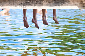 Boy´s Legs Dangling Down from Wooden Pier over Water