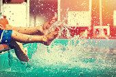 Boys legs splashing water in pool, summer holiday vintage