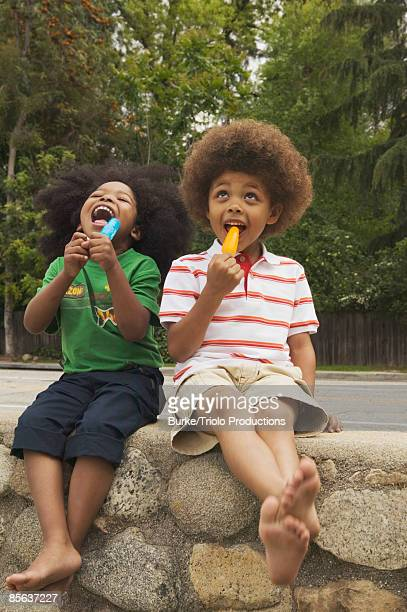Boys licking flavored ice pops