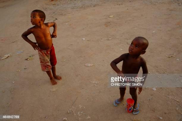 Boys look at a flying kite at the Cidade de Deus shantytown in Rio de Janeiro on January 23 2014 AFP PHOTO / Christophe Simon