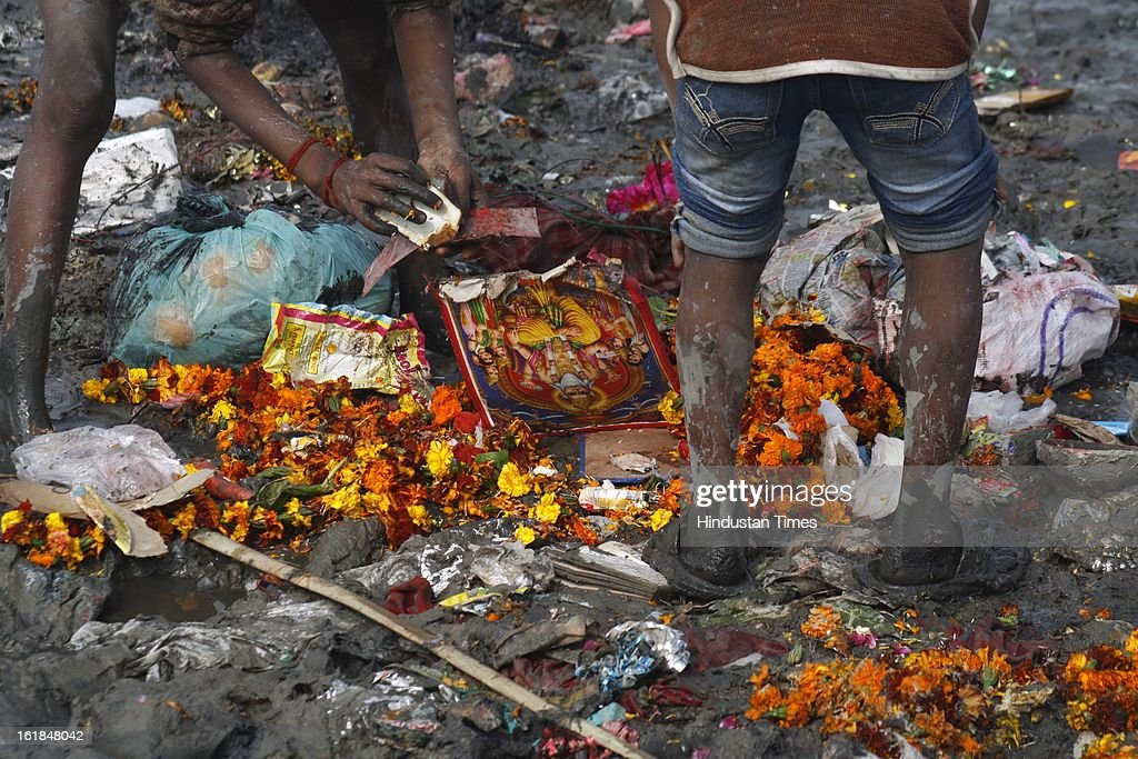 Boys look for the coins and other offerings amongst the remains of idols of the goddess Saraswati that were immersed by devotees into the water of the river Yamuna on the occasion of Vasant Panchami festival on February 17, 2013 in Noida, India. Vasant Panchami sometimes referred to as Saraswati Puja or Shree Panchami, is a Hindu festival. On this day Hindus worship Saraswati, the goddess of knowledge, music, art and culture. This festival is celebrated every year on the 5th day or Panchami of the bright fortnight of the lunar month of Magha, which falls during January-February.