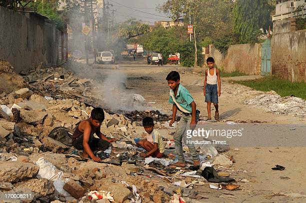 Boys look for the things amongst the wastage thrown on a road on the ocassion of World Environment Day on June 5 2013 in Noida India The World...