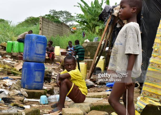 Boys look on as residents of a shanty town in Abidjan sort through the remains of their homes on May 26 2017 in Abidjan following the death of 5...