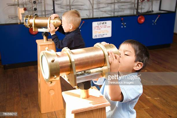 Boys looking through telescopes at museum