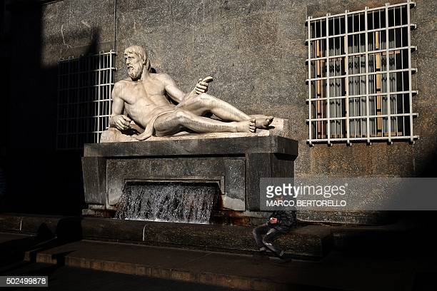 TOPSHOT A boys looks at his cell phone near a statue in Turin on December 26 2015 AFP PHOTO / MARCO BERTORELLO / AFP / MARCO BERTORELLO
