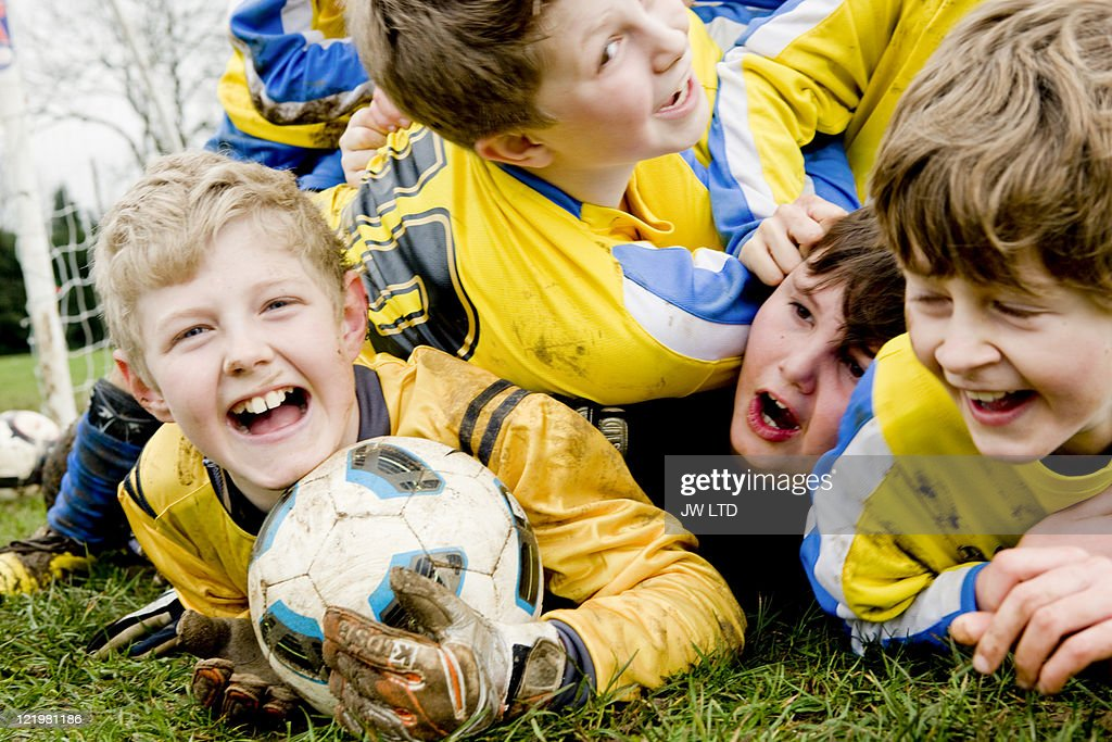 Boys lying on grass with football : Stock Photo