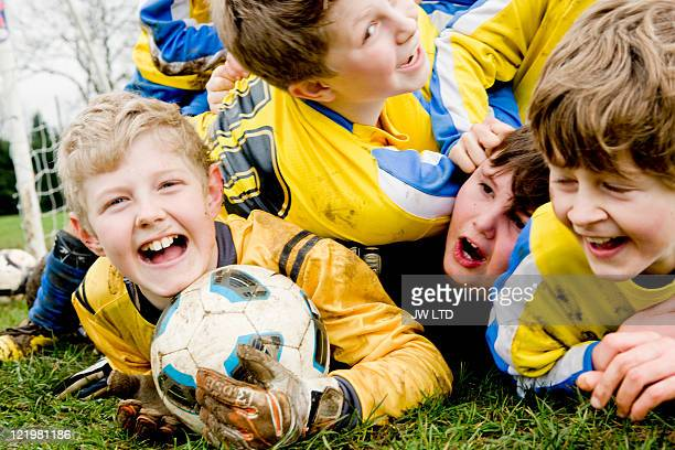 Boys lying on grass with football