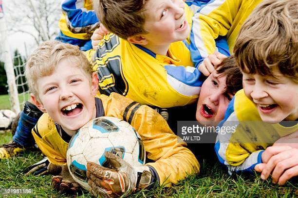 Boys lying on grass with football
