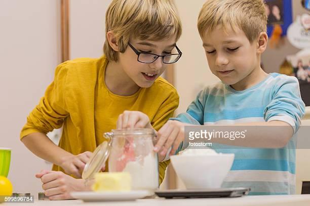 Garçons mesure de farine sur le pèse-personne dans la cuisine