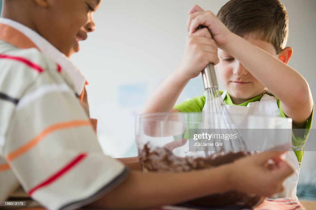 Boys mixing cake batter together : Stock Photo