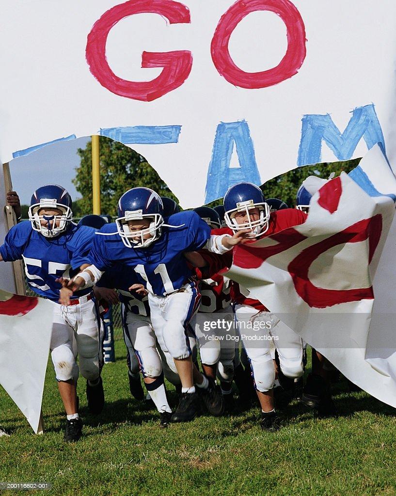 Boys (10-12) on pee wee football team breaking through banner