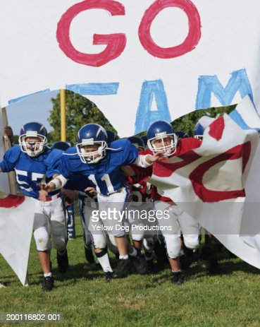 Boys (10-12) on pee wee football team breaking through banner : Stock Photo