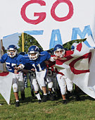 Boys (10-12) on pee wee football team breaking through banner