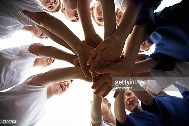 Boys (9-11) on soccer team putting hands in, view from below