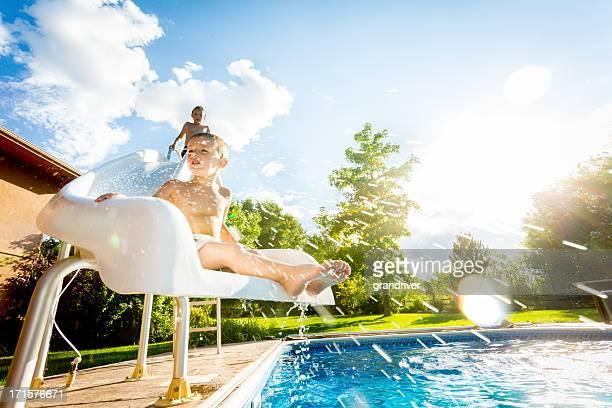 Boys on swimming pool slide