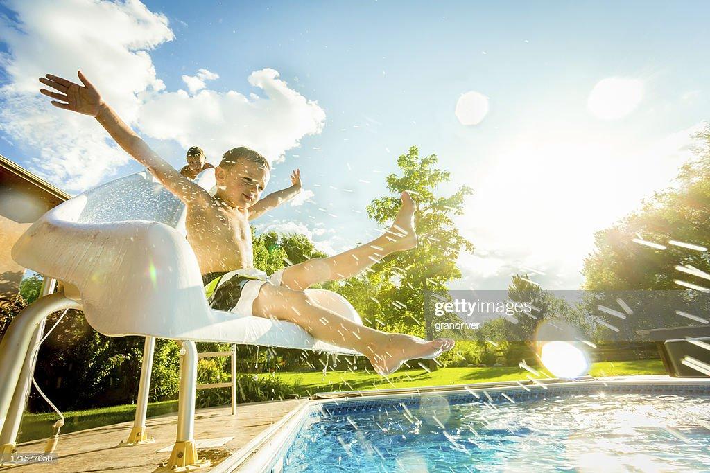 Boys on swimming pool slide : Stock Photo