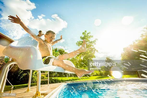 Jungen auf Swimmingpool und Wasserrutsche