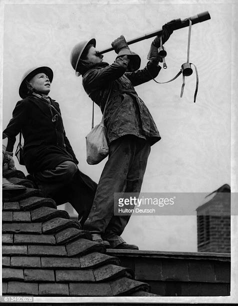 Boys on the roof of Strodes School in Egham England practice using a telescope to spot enemy aircraft during World War II