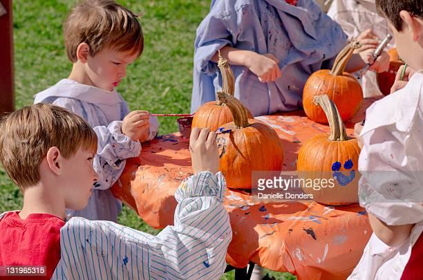 Boys painting on pumpkin