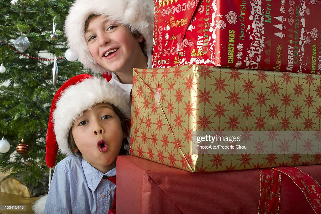 Boys peeking around stack of Christmas presents