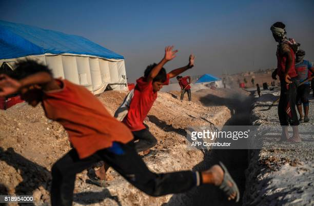 TOPSHOT Boys play as workers dig a trench for the sewage system of a temporary camp for displaced people near the northern Syrian village of Ain Issa...