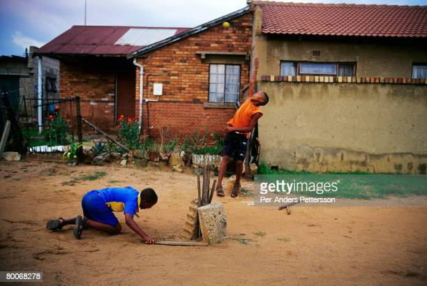 Boys play cricket on the street as the sun sets on May 10 2005 in Soweto Johannesburg South Africa Soweto is South Africa's largest township and it...