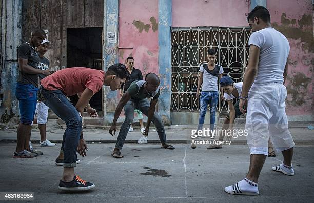 Boys play 'Efecto' a game regarded as Cuba's tennis by Cubans at a street in Havana capital city of Cuba on February 9 2015 Cubans continue their...