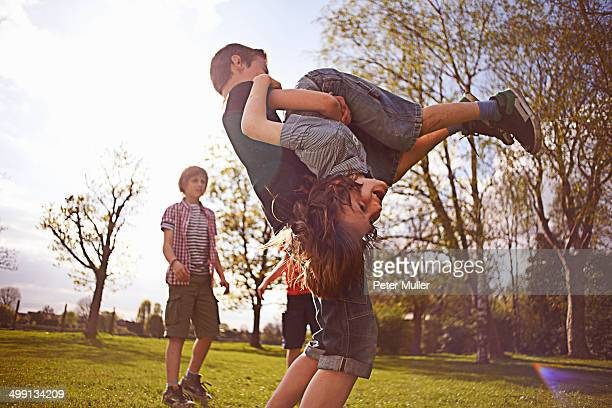 Boys play fighting on playing field