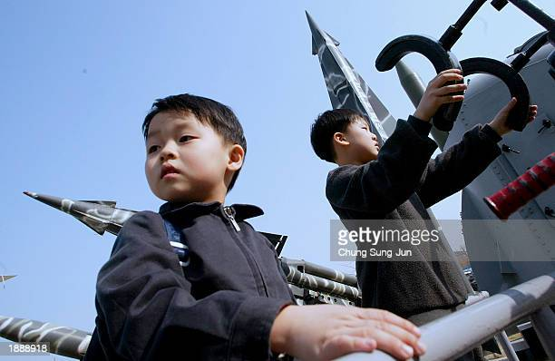 Boys play in front of North Korean and South Korean missiles at the Korea War Memorial Museum April 1 2003 in Seoul South Korea According to...