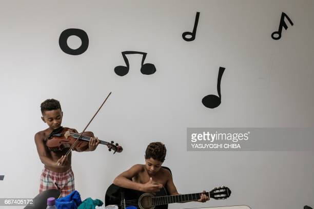 Boys play instruments in a free music class inside a station of the cable car system which is no longer running over the Alemao favela in Rio de...