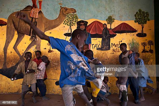 Boys play soccer near a Tuareg desert mural in the center of Timbuktu the mythical Northern Mali city 22 January 2010