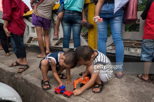 Boys play with their toys as others watch as their houses are torn down in the evicted area of the Bukit Duri neighbourhood located on the Ciliwung...