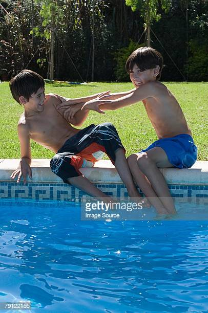 Jungen playfighting am pool