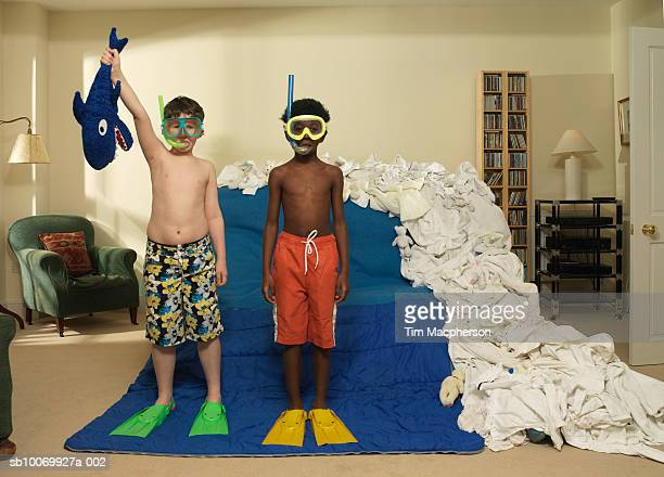 Boys (9-10) playing as snorkelers in living room