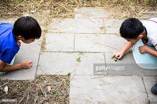 Boys playing colorful marbles on ground