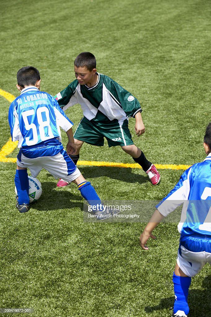 Boys (7-9) playing football, elevated view : Stock Photo