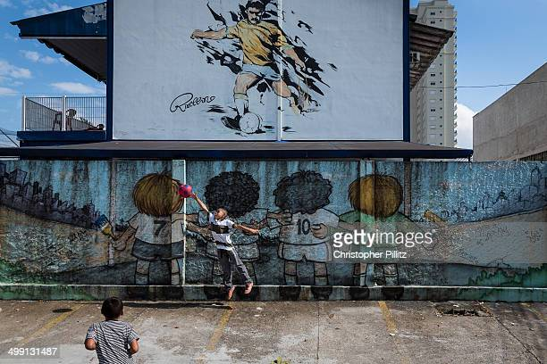 Boys playing football in front of graffited wall