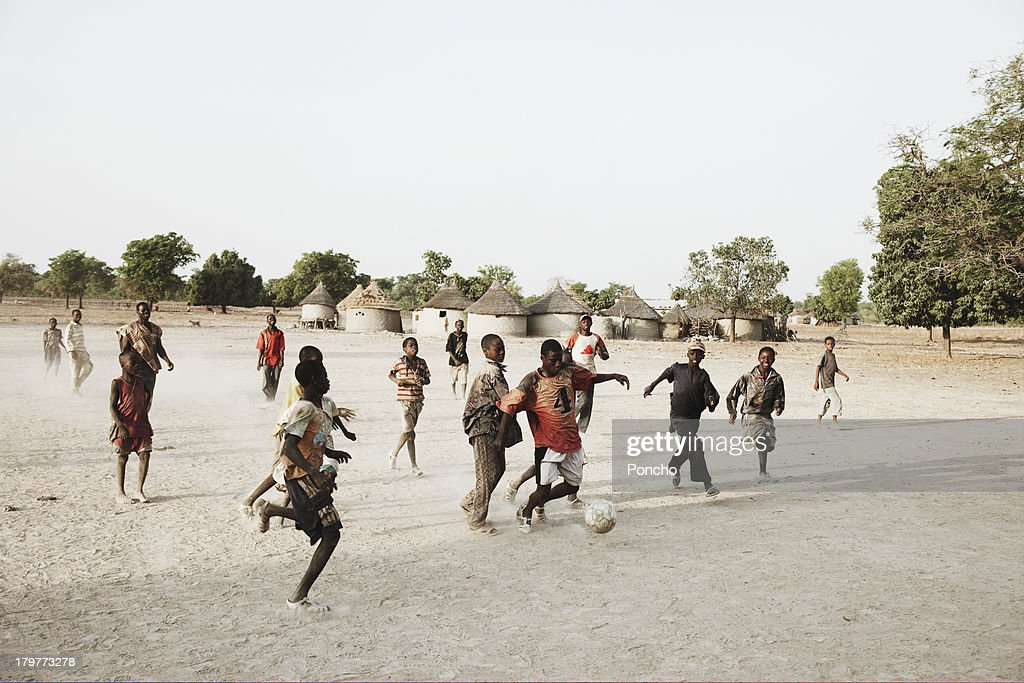 boys playing football in their village : Stock-Foto
