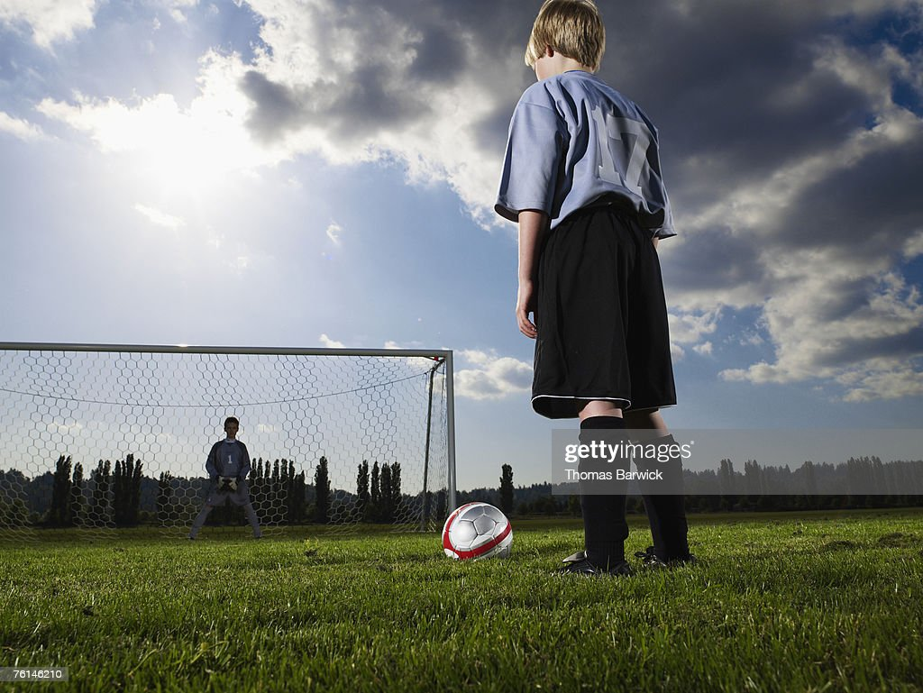 Boys (10-11, 12-13) playing football on pitch, rear view, low angle : Stock Photo