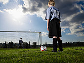 Boys (10-11, 12-13) playing football on pitch, rear view, low angle