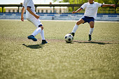 Portrait of two boys playing football, fighting for ball during junior football match in field