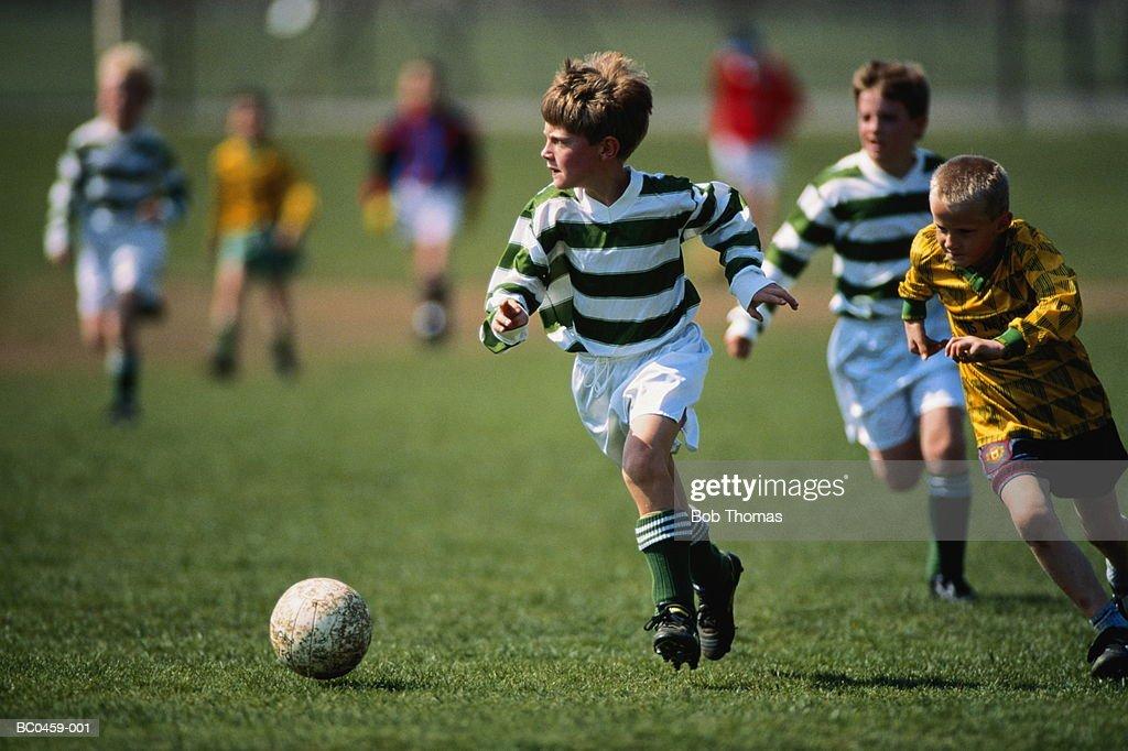 Boys (7-9) playing football : Stock Photo