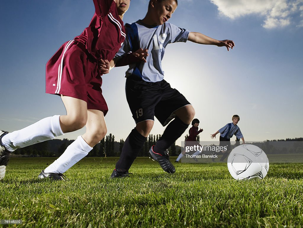 Boys (10-13) playing football, two running after ball, on pitch : Stock Photo
