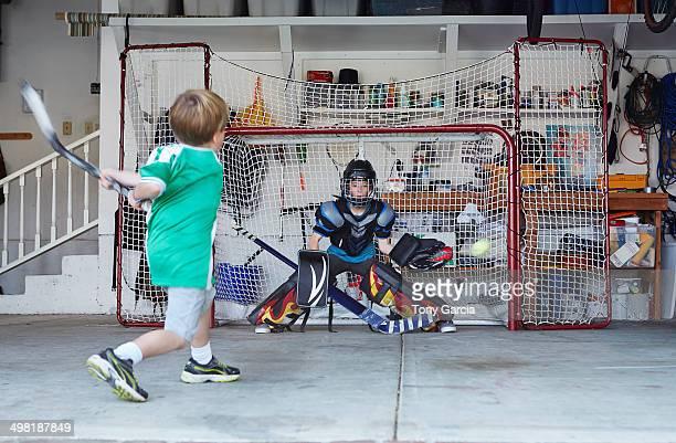 Boys playing hockey in garage
