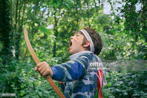 Boys playing in forest with bow and arrow