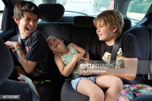 3 boys playing in the back seat of a car