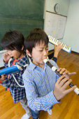 Boys playing musical instruments in classroom